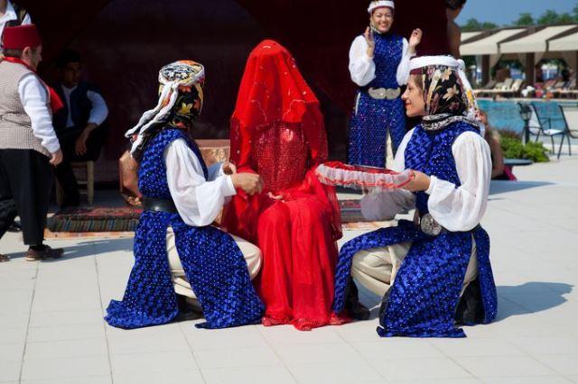 Девушки растирают руки невесты хной
